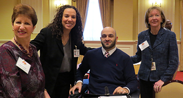Three woman standing and one man in a chair, in a room at the Annapolis Senate buidling.