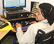 A young man in a wheelchair using a computer with assistive technology.